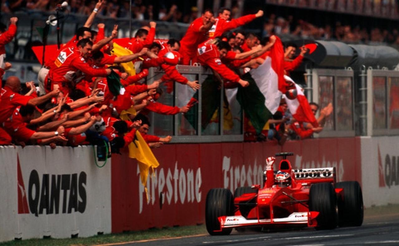 Michael Schumacher taglia il traguardo del GP del Giappone 2000 in prima posizione, con gli uomini in rosso in festa